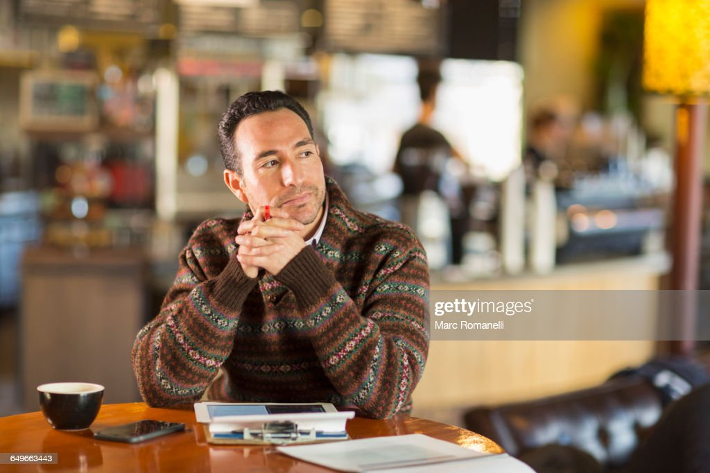 Hispanic businessman using digital tablet in coffee shop : Photo