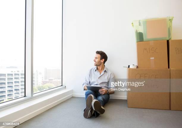 Hispanic businessman using digital tablet in new office