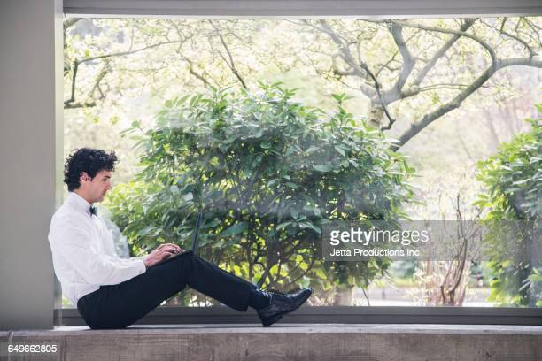 Hispanic businessman using laptop in window