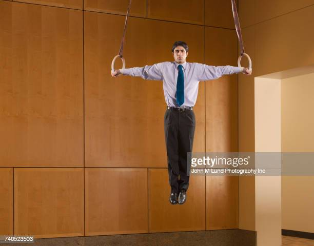 Hispanic businessman using on gymnastic rings