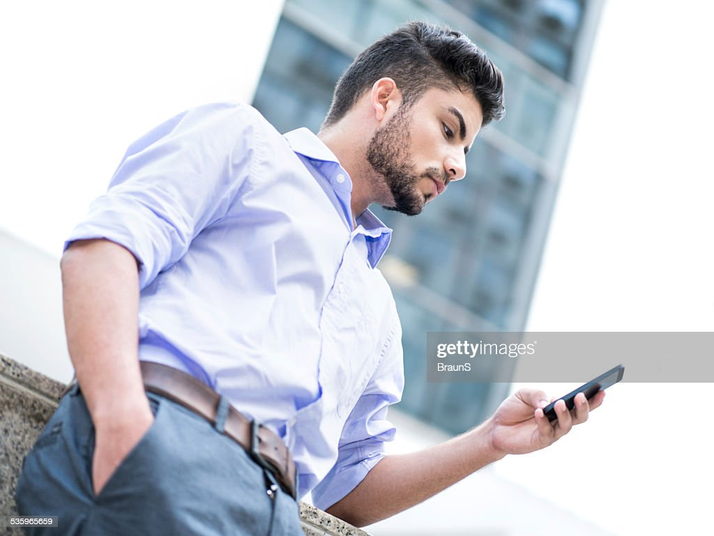 Hispanic businessman using smart phone outdoors. : Stock Photo