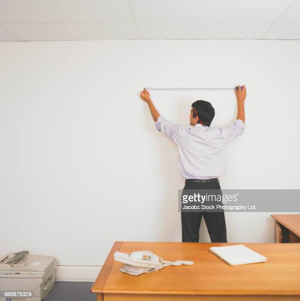 Hispanic businessman using tape measure to measure wall