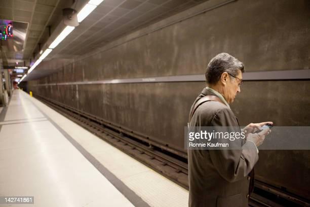Hispanic businessman waiting in subway using cell phone