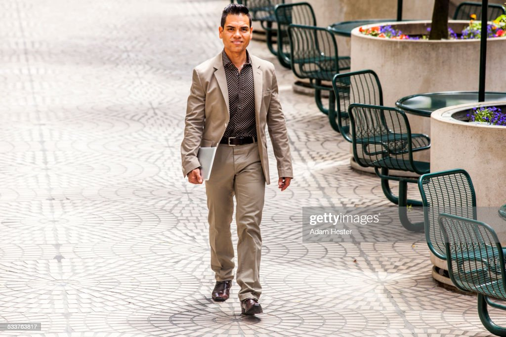 Hispanic businessman walking in courtyard : Foto stock