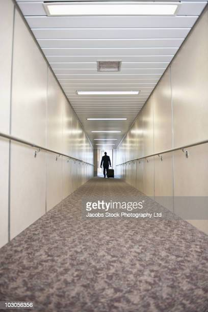 Hispanic businessman walking through jetway