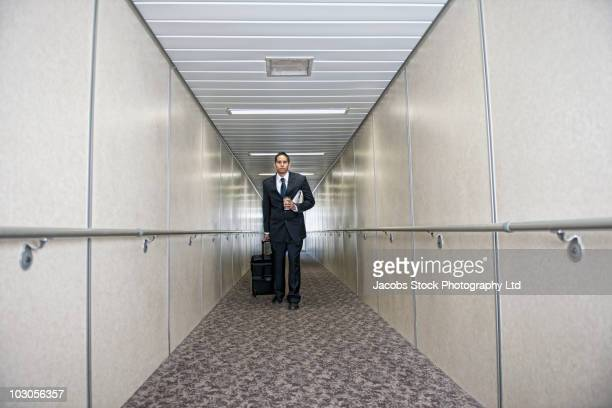 hispanic businessman walking through jetway - passenger boarding bridge stock pictures, royalty-free photos & images