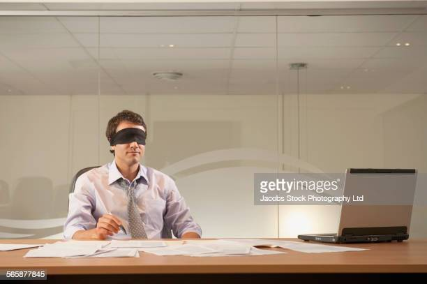 Hispanic businessman wearing blindfold in office