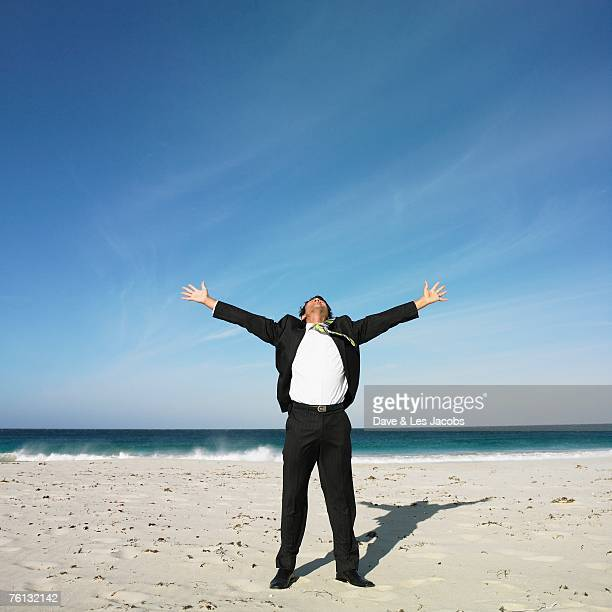 Hispanic businessman with arms outstretched at beach