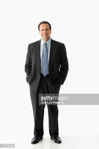 Hispanic businessman with hands in pockets