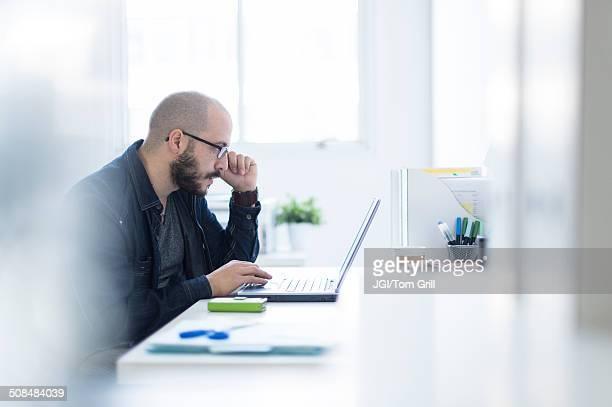 hispanic businessman working at desk - só um homem imagens e fotografias de stock