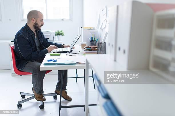 hispanic businessman working at desk - lunettes de lecture photos et images de collection