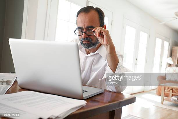 hispanic businessman working from home on computer - reading glasses stock pictures, royalty-free photos & images