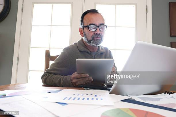 hispanic businessman working from home on computer - baby boomer stock pictures, royalty-free photos & images