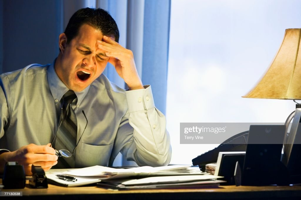 Hispanic businessman yawning at desk : Stock Photo
