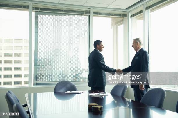 hispanic businessmen shaking hands in conference room - sells arizona stock pictures, royalty-free photos & images