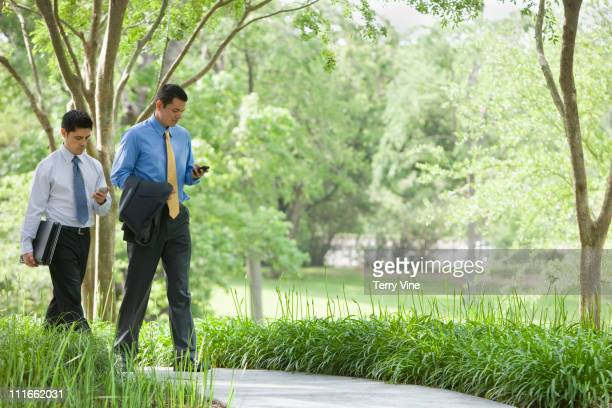 Hispanic businessmen using cell phones in park
