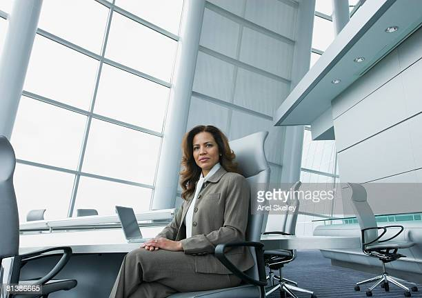 hispanic businesswoman at conference table - directrice photos et images de collection