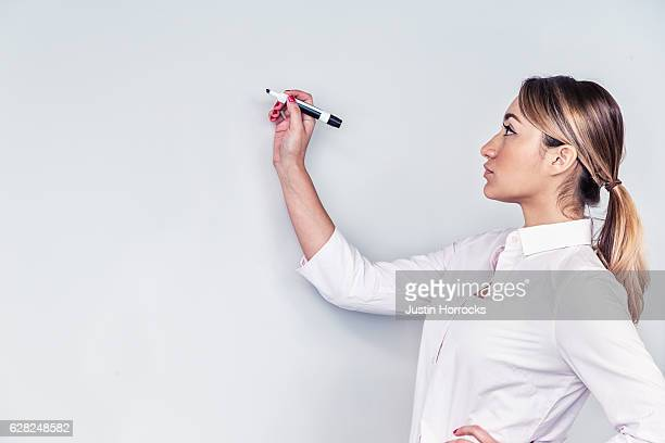 Hispanic Businesswoman at Whiteboard with Marker
