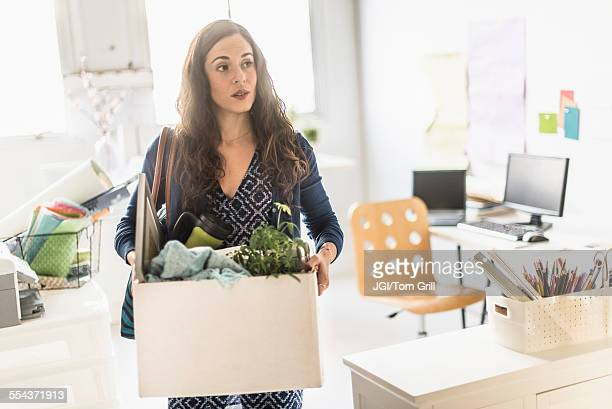 hispanic businesswoman carrying cardboard box in office - downsizing unemployment stock pictures, royalty-free photos & images