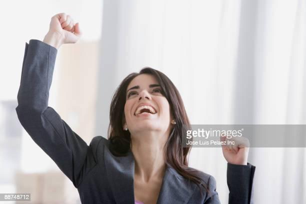 Hispanic businesswoman cheering