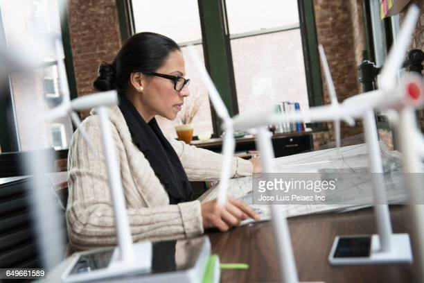 Hispanic businesswoman examining blueprints in office