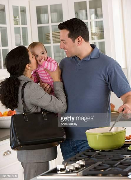 Hispanic businesswoman greeting family in kitchen