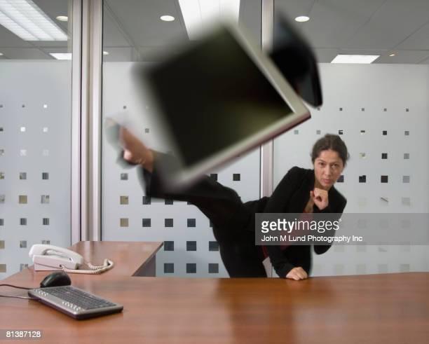 Hispanic businesswoman kicking laptop