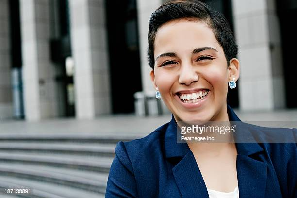 Hispanic businesswoman laughing outdoors