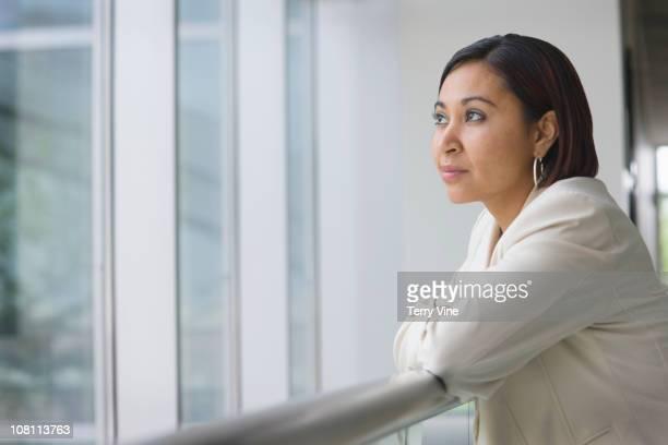 Hispanic businesswoman leaning against railing
