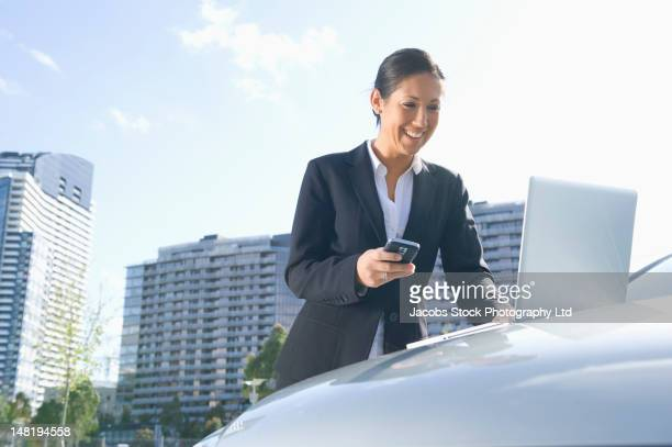 Hispanic businesswoman leaning on car using laptop and cell phone