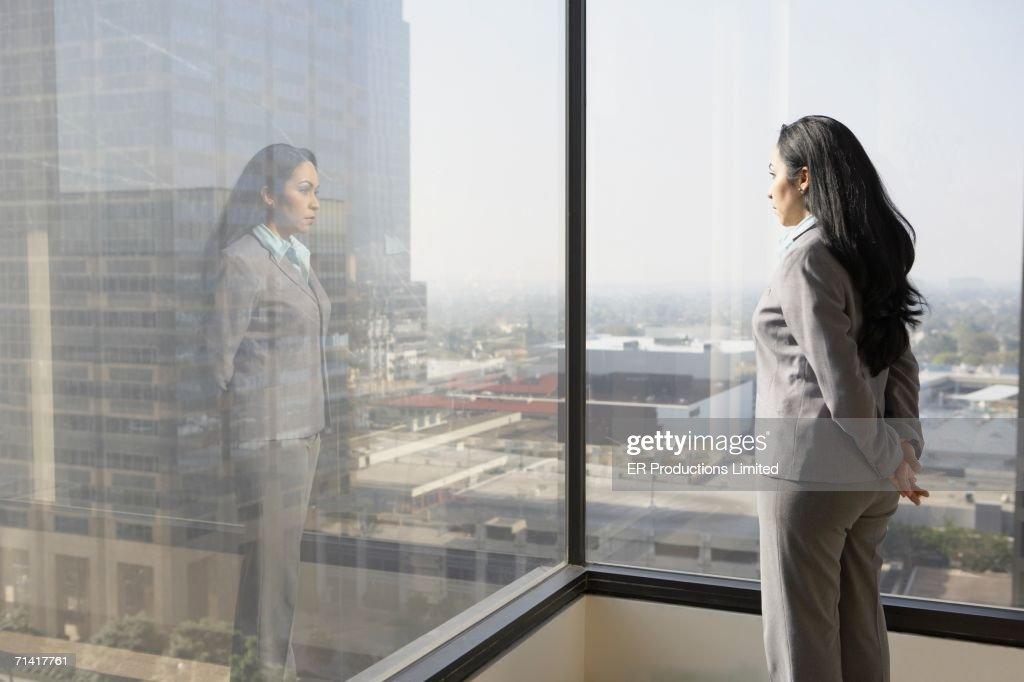 Hispanic businesswoman looking out a window : Stockfoto