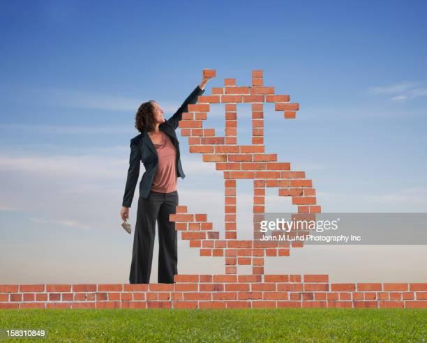 Hispanic businesswoman making dollar sign with bricks