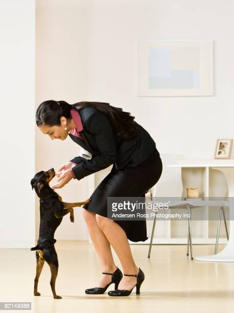 Hispanic businesswoman petting dog