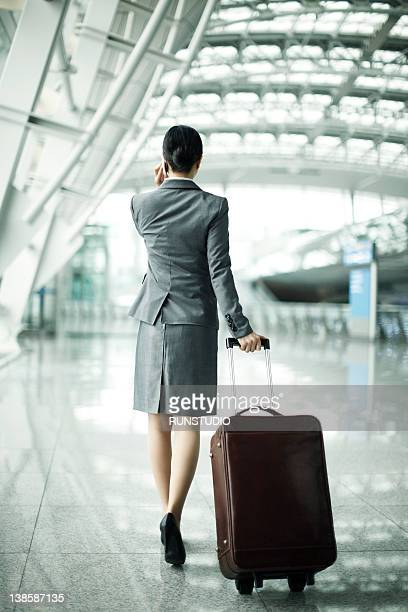 Hispanic businesswoman pulling suitcase