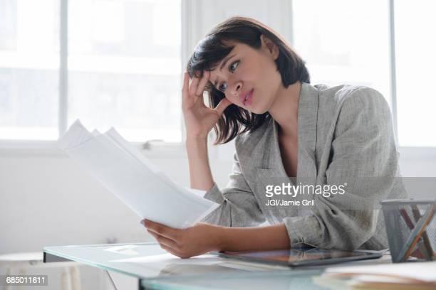 Hispanic businesswoman reading paperwork