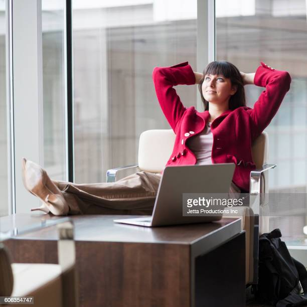 Hispanic businesswoman relaxing in office lounge