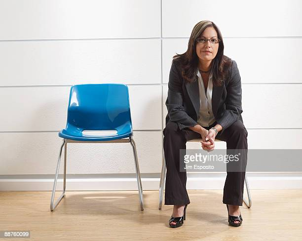 hispanic businesswoman sitting in waiting room - sitzen stock-fotos und bilder