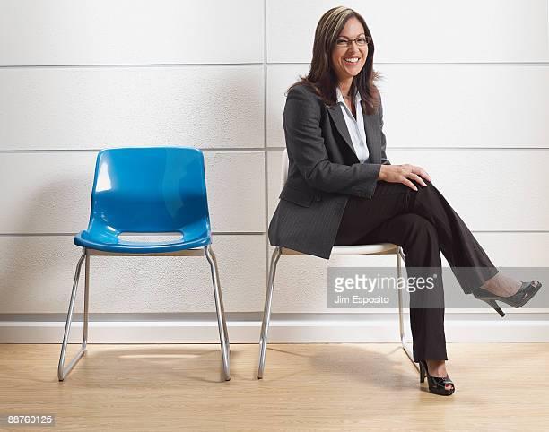 Hispanic businesswoman sitting in waiting room
