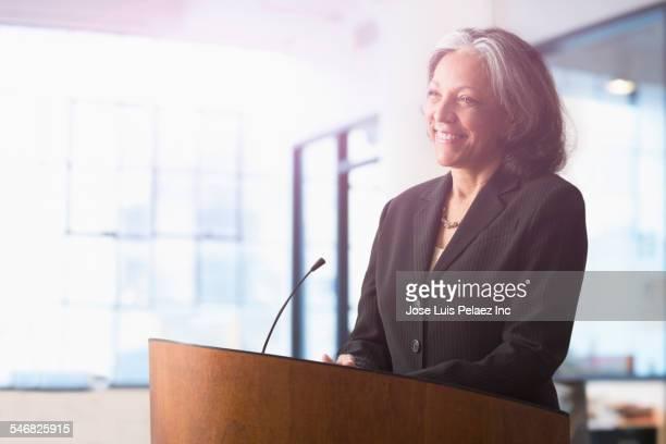 hispanic businesswoman speaking at podium - 番組司会者 ストックフォトと画像