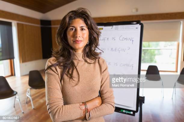 Hispanic businesswoman standing in meeting room