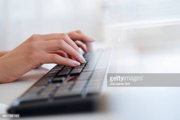 hispanic businesswoman typing on keyboard - computertoetsenbord stockfoto's en -beelden