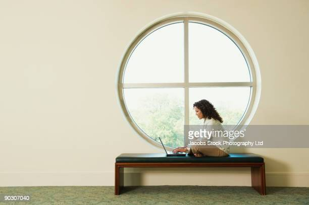 hispanic businesswoman typing on laptop in corridor - circle stock pictures, royalty-free photos & images
