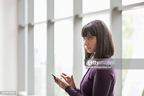 Hispanic businesswoman using cell phone in office