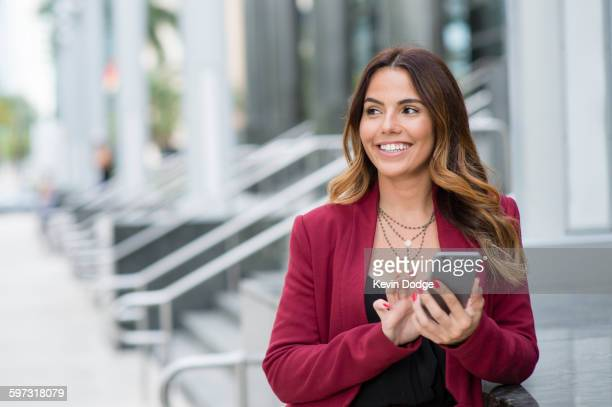Hispanic businesswoman using cell phone outdoors