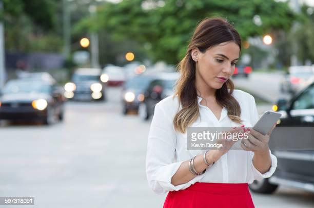 Hispanic businesswoman using cell phone outdoors