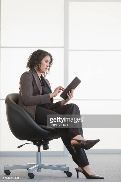 Hispanic businesswoman using digital tablet