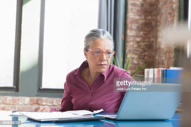 hispanic businesswoman using laptop in office - reading glasses stock pictures, royalty-free photos & images