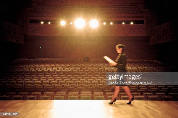 Hispanic businesswoman walking across stage in empty auditorium