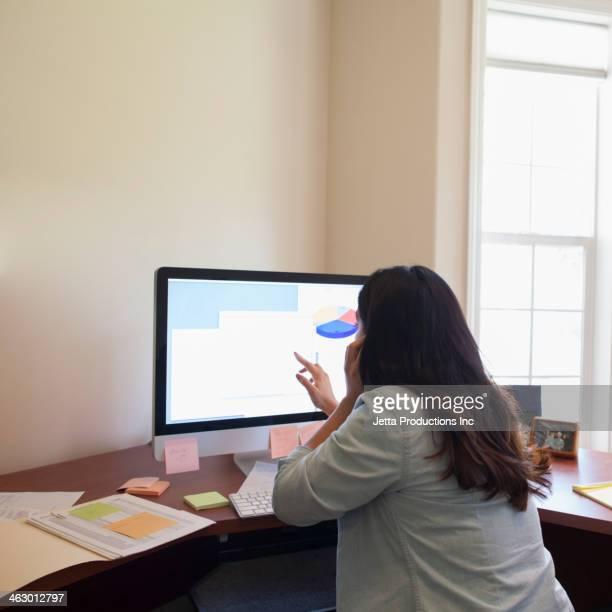 hispanic businesswoman working on computer - looking over shoulder stockfoto's en -beelden