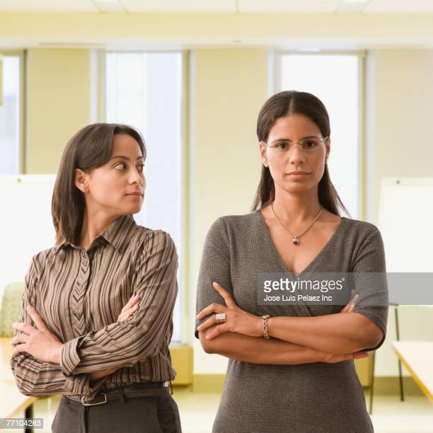 Hispanic businesswomen with arms crossed